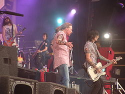 Guns N' Roses in 2006 at the Download Festival. From left to right: Tommy Stinson, Axl Rose, Richard Fortus.